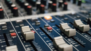Faders on a mixing/mastering desk